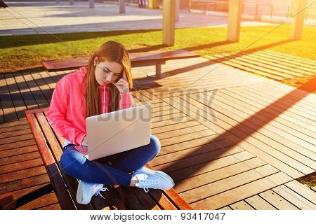 Girl freelance works in the Internet outdoors holding open laptop computer on his knees