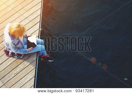 Young girl sitting on a wooden pier holding a touch tablet with blank black screen