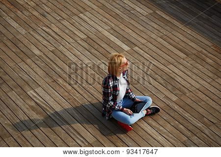 Young tourist sitting on a wooden floor with a tablet in hand enjoying rest and looks aside