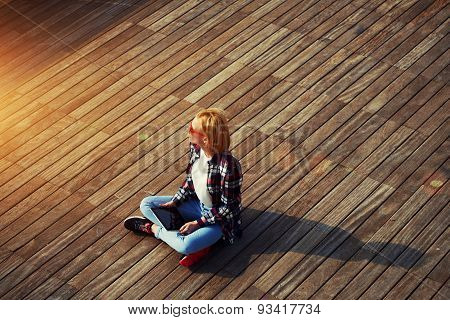 Portrait of a young attractive girl sitting on a wooden floor with a tablet in hands and looks aside