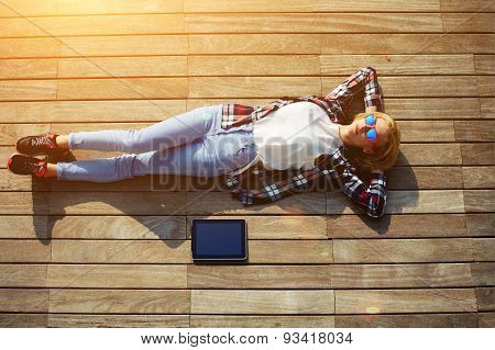 Active young tourist lying on a wooden floor with a tablet enjoying the good weather