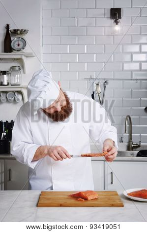 Professional chef cook in uniform diligently cutting salmon fish on fillets at kitchen