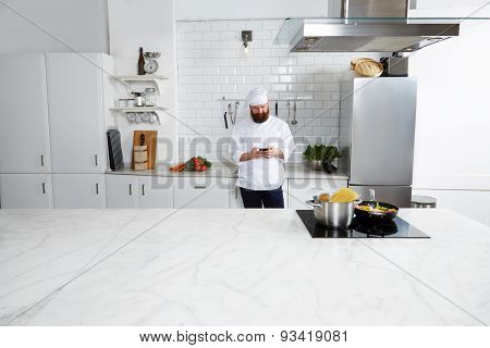 Chef cook use his cell phone while preparing italian pasta meal on big kitchen