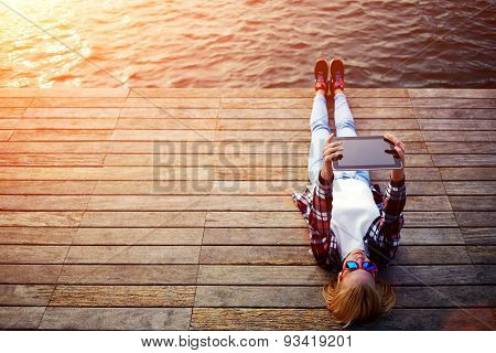 Young hipster girl lying on a wooden pier and makes self portrait on the touch tablet