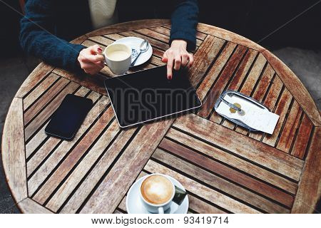 Girl girl sitting and using touch screen tablet while drink coffee bill check and mobile phone near