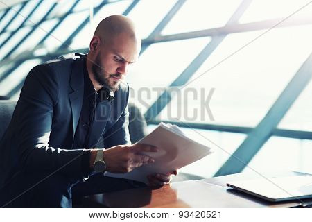 Elegant adult male businessman sitting in his office and read financial documents
