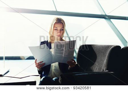 Young active business lady working with document at a big light office