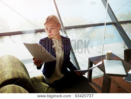 Portrait of young attractive businesswoman  sitting next to the window read some documents.