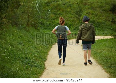 Rear view couple hiking on a mountain trail together friends carrying backpacks walking outdoors