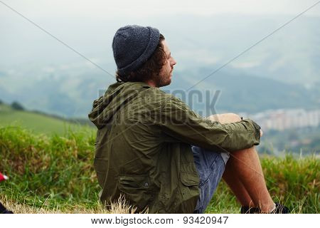 Young man relaxing on the grass, enjoying the outdoors and pastime after going way