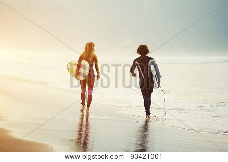 Rearview shot of a couple in wetsuits walking along beautiful seashore holding their surfboards