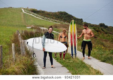 Group of three surfers walking down nature road relaxing after surf