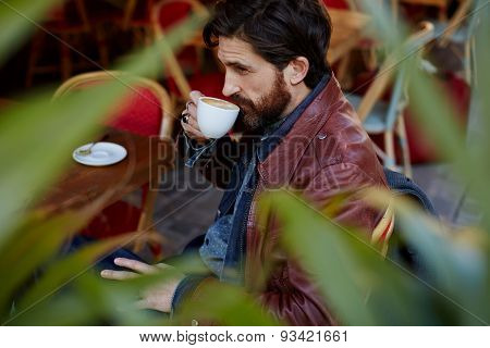 Side view through plant leaves pensive fashionable hipster man holding cup of tea next to mouth