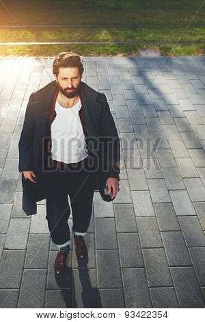 Portrait stylish hipster man walking on the street at sunny evening filter and flare sun