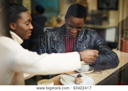 Two young friends talk and drink coffee in cafe beautiful place cold winter days indoors