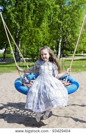 Little Girl On The Round Swings Posing