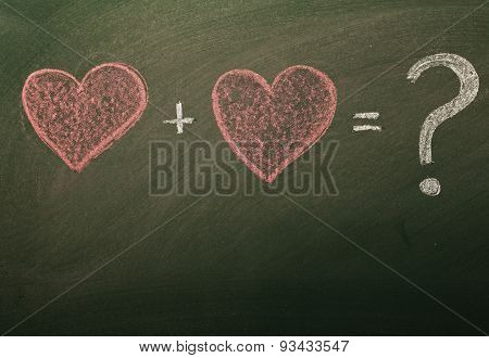 sketch of two hearts and question mark sign on blackboard