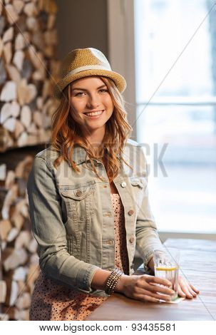 people, drinks, alcohol and leisure concept - happy young redhead woman drinking water at bar or pub