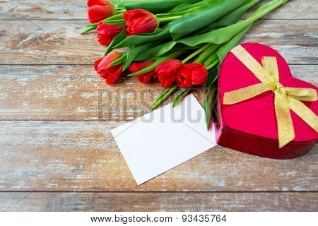 flowers, valentines day, greeting and holidays concept - close up of red tulips, blank letter and heart shaped chocolate box on wooden table