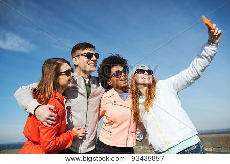 people, leisure, friendship and technology concept - group of smiling teenage friends taking selfie with smartphone outdoors