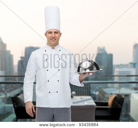 cooking, profession and people concept - happy male chef cook holding cloche over city restaurant lounge background