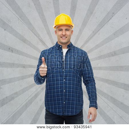 repair, construction, building, people and maintenance concept - smiling male builder or manual worker in helmet showing thumbs up over gray burst rays background