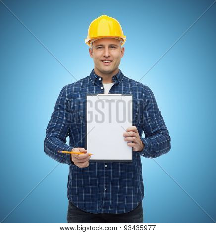 repair, construction, building, people and maintenance concept - smiling male builder or manual worker in helmet showing blank paper on clipboard over blue background