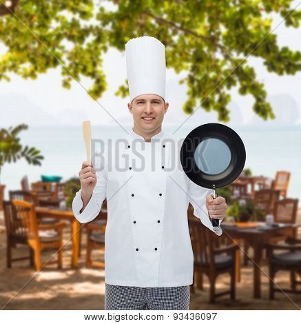 cooking, profession and people concept - happy male chef cook holding frying pan and spatula over restaurant lounge on beach