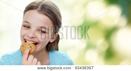 people, happy childhood, food, sweets and bakery concept - smiling little girl eating cookie or biscuit over green natural background