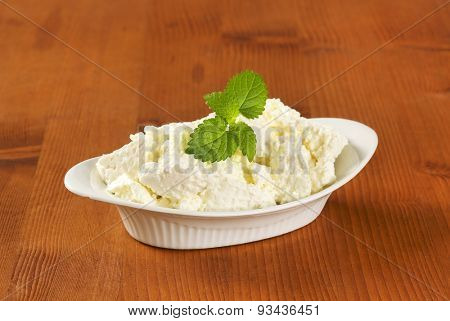 bowl of fresh curd cheese and mint on wooden table