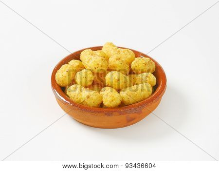 bowl of peanut crisps on white background