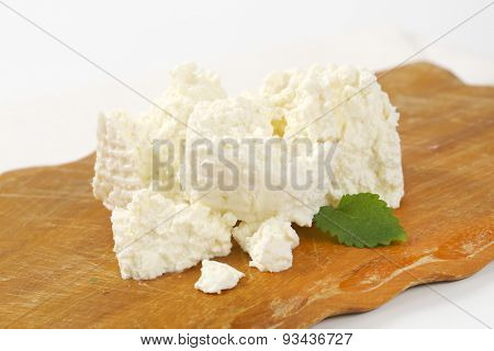 slices of fresh curd cheese on wooden cutting board