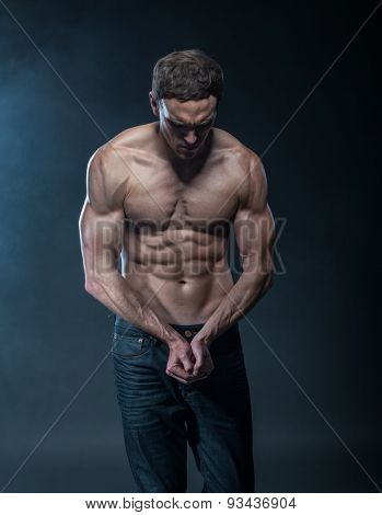 Portrait of a muscular male model against dark background with smoke.