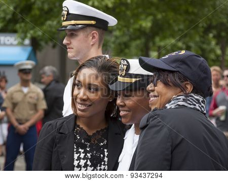 NEW YORK - MAY 22 2015: A newly promoted US Navy officer poses for a photograph with family after the promotion ceremony at the National September 11 Memorial site during Fleet Week 2015.