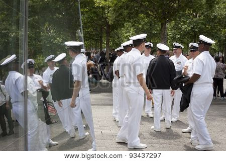 NEW YORK - MAY 22 2015: Reflection of US Navy officers in the glass of the the National September 11 Museum as they gather for the military re-enlistment and promotion ceremony during Fleet Week 2015.