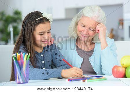 Little girl drawing wuth grandma