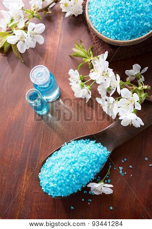 Mineral bath salts, shower gel, towels and flowers on the wooden table. Spa concept