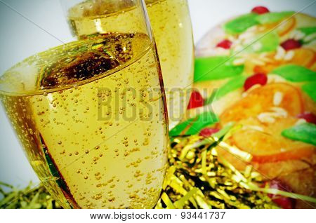 closeup of two glasses with champagne and a coca de Sant Joan, a typical sweet flat cake from Catalonia, Spain eaten on Saint Johns Eve