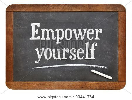Empower yourself motivational phrase - text on an isolated  vintage slate blackboard