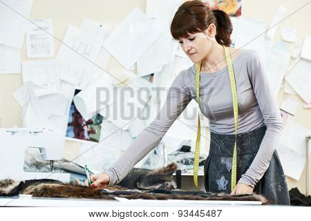young female tailor designer working with cloth fabric in workshop