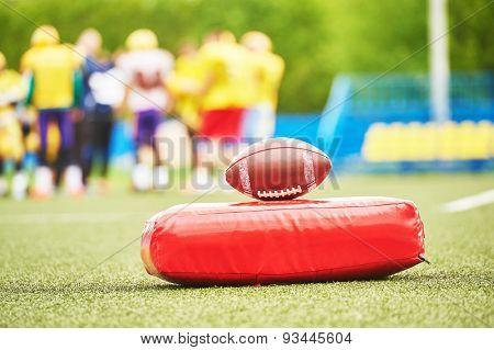 American football ball with training equipment lying on field grass