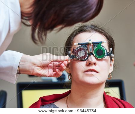 Optometry concept. female doctor ophthalmologist or optometrist helps young woman with phoropter during sight testing or eye examinations in clinic