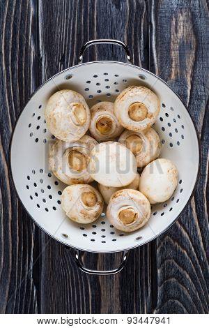 Fresh white champignons on dark wooden table