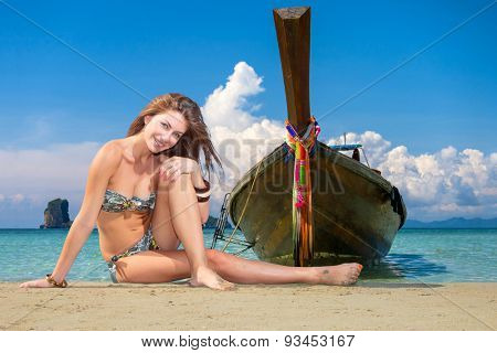 Beautiful woman on the beach posing by a long tail boat in Thailand.