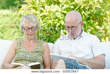 A Man Looks At A Digital Tablet And His Wife Is Reading A Book