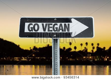 Go Vegan direction sign with sunset background