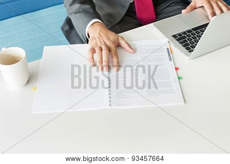 Cropped image of businessman with book and laptop at desk