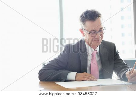 Mature businessman writing on book at table in office