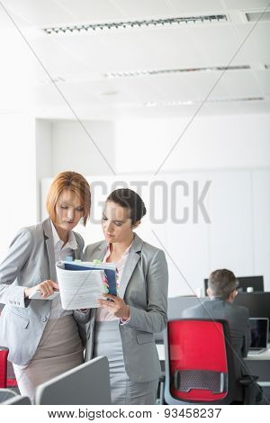 Businesswoman discussing over book in office