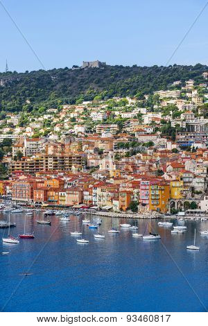 VILLEFRANCHE-SUR-MER, FRANCE - OCTOBER 1, 2014: Coast view of picturesque French Riviera town with leisure boats anchored in harbor and fort Mont Alban on hill.